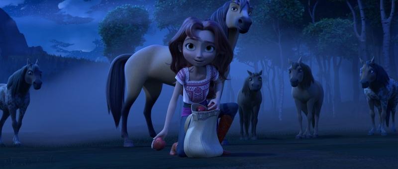 Lucky Prescott (Isabela Merced, center) kneels in front of Spirit (center) and his herd in DreamWorks Animation's Spirit Untamed, directed by Elaine Bogan.